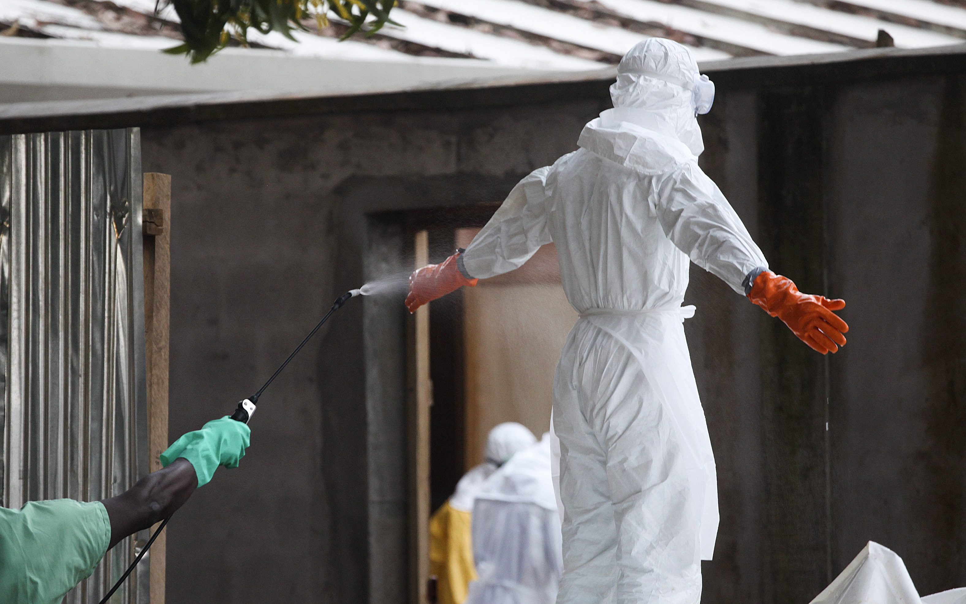 epa04339981 A photograph made available 03 August 2014 shows a Liberian nurse in protective clothing being sprayed with disinfectant after preparing several bodies of victims of Ebola for burial in the isolation unit of