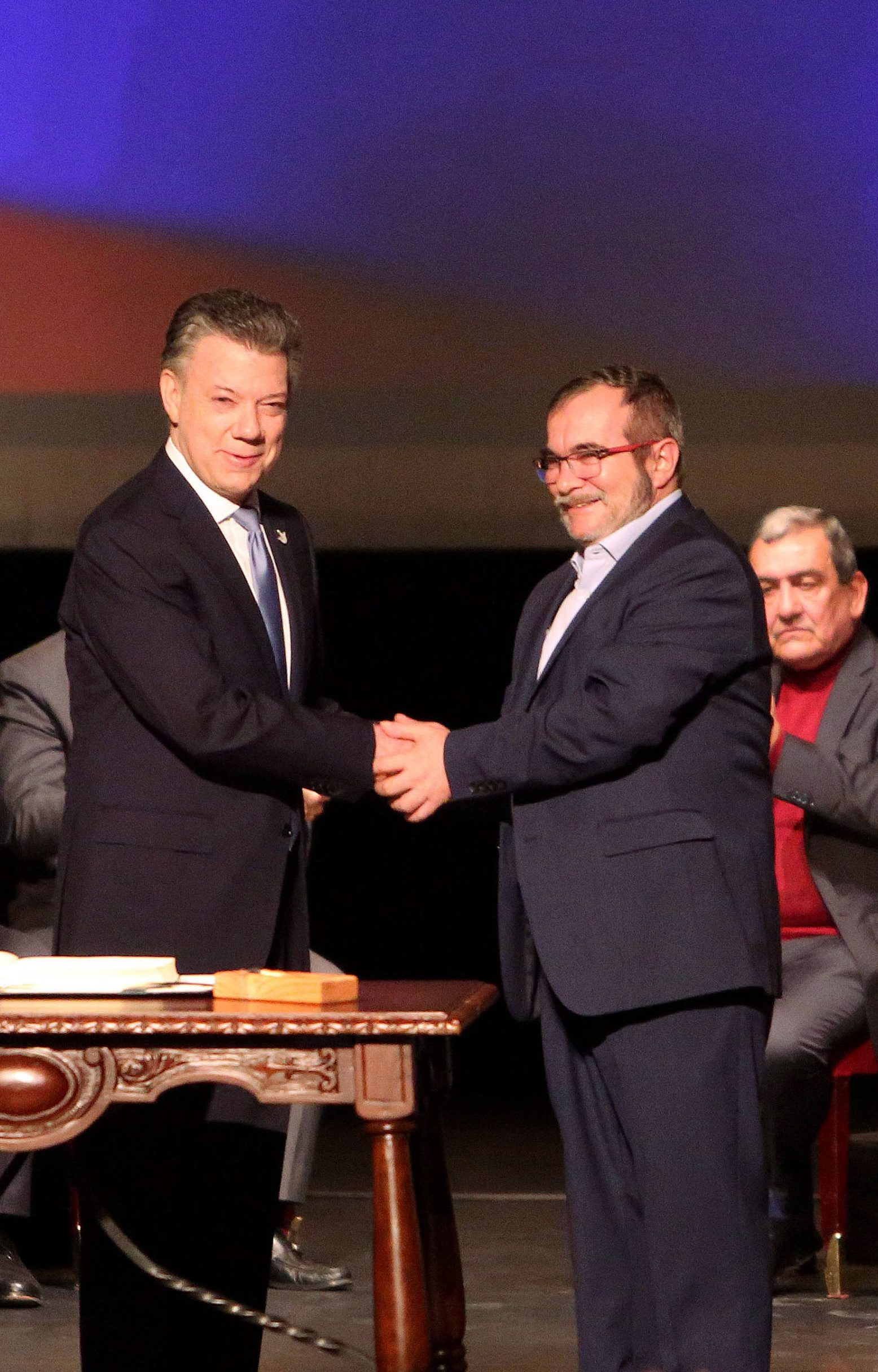 President of Colombia Juan Manuel Santos (L) and Chief of the FARC Rodrigo Londono Echeverry a.k.a. 'Timochenko' (R) shake hands after signing the new peace agreement 24 novembro 2016