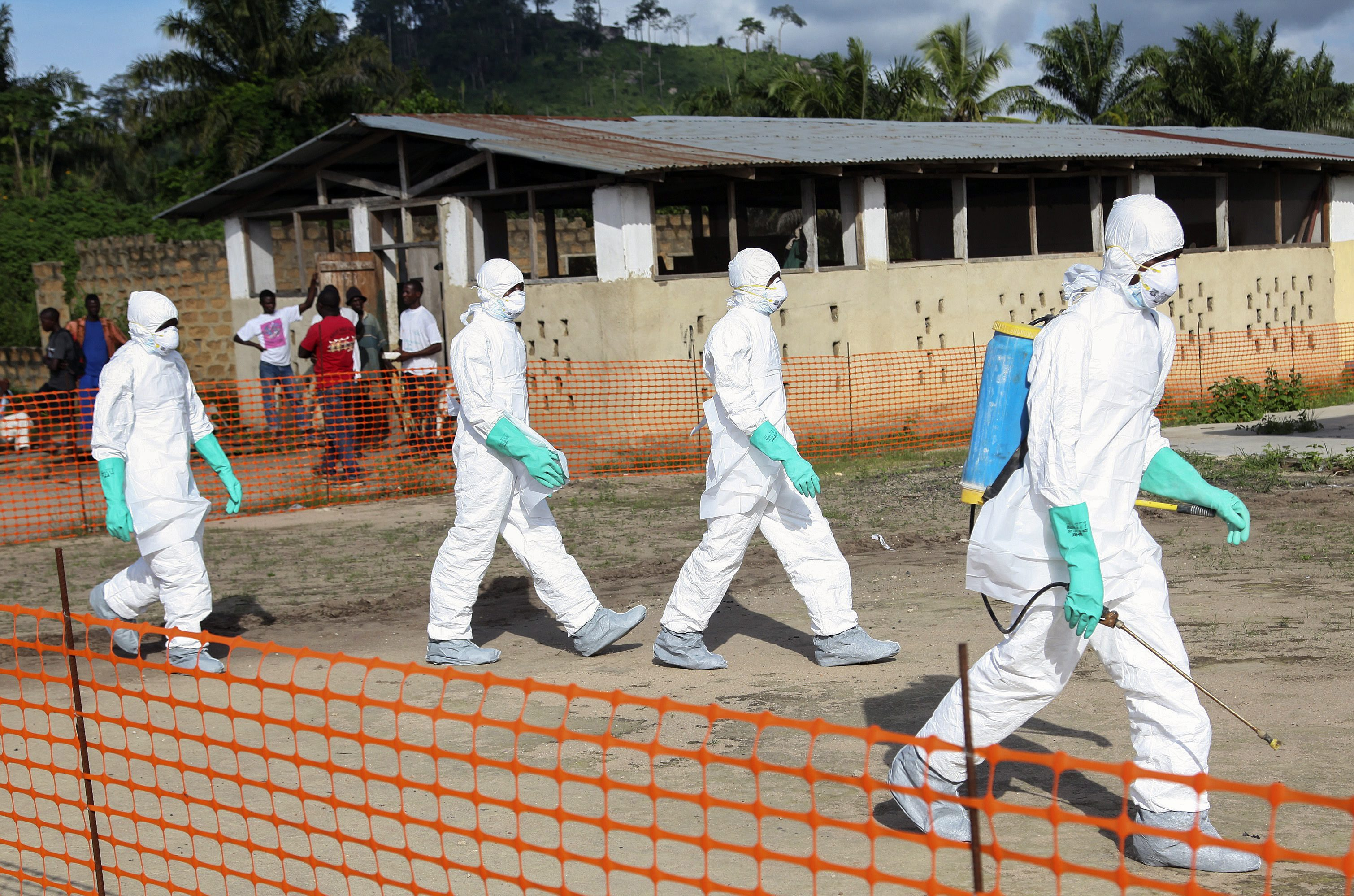 epa04332724 A photograph made available 27 July 2014 shows Liberian health workers in protective gear on the way to bury a woman who died of the Ebola virus from the isolation unit in Foya, Lofa County, Liberia, 02 July