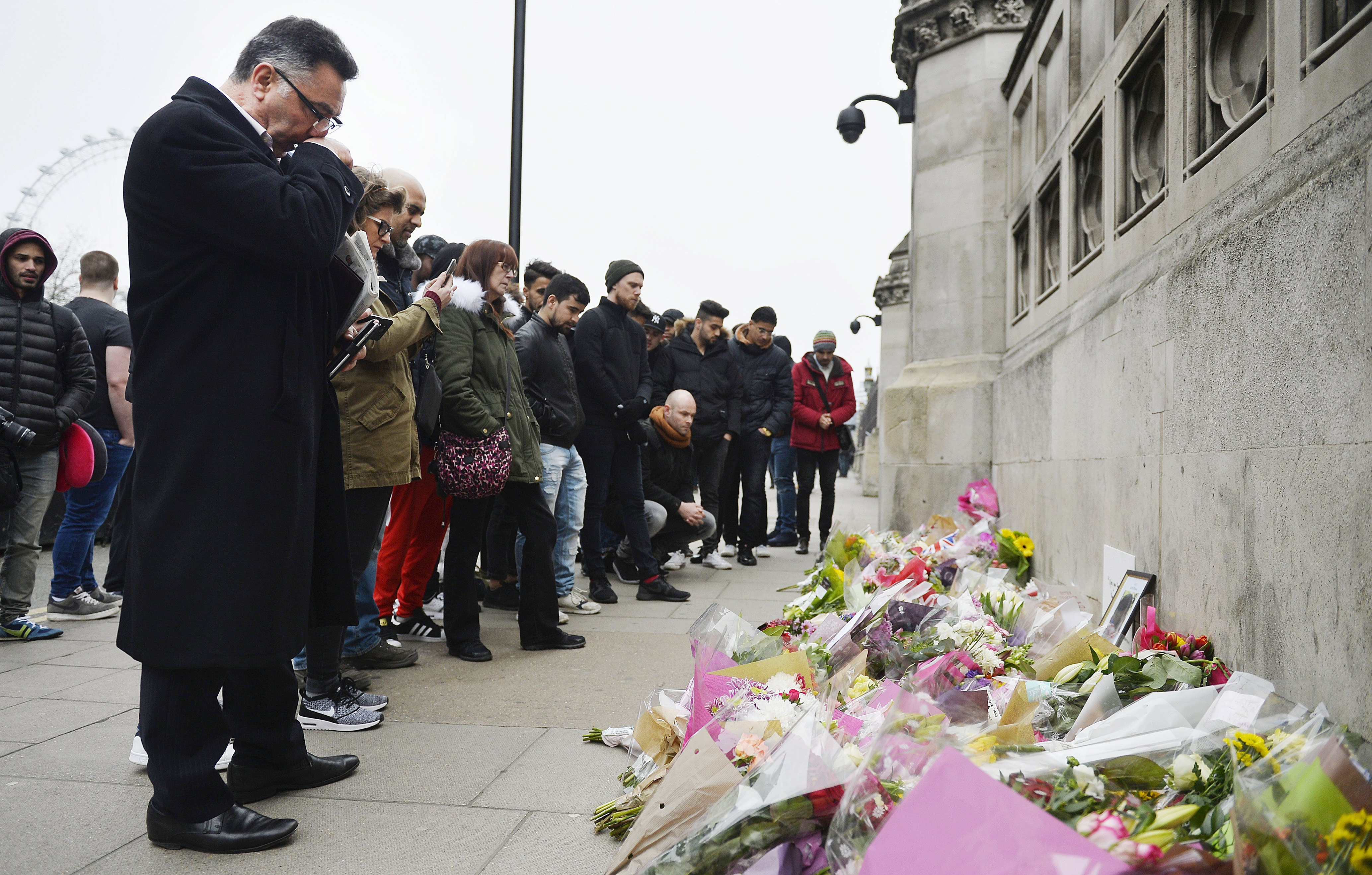 epa05867529 People look at flowers laid in Westminster near to the scene of incidents on 22 March in central London, Britain, 24 March 2017. Scotland Yard said on 24 March 2017 that police have made nine arrests in rela