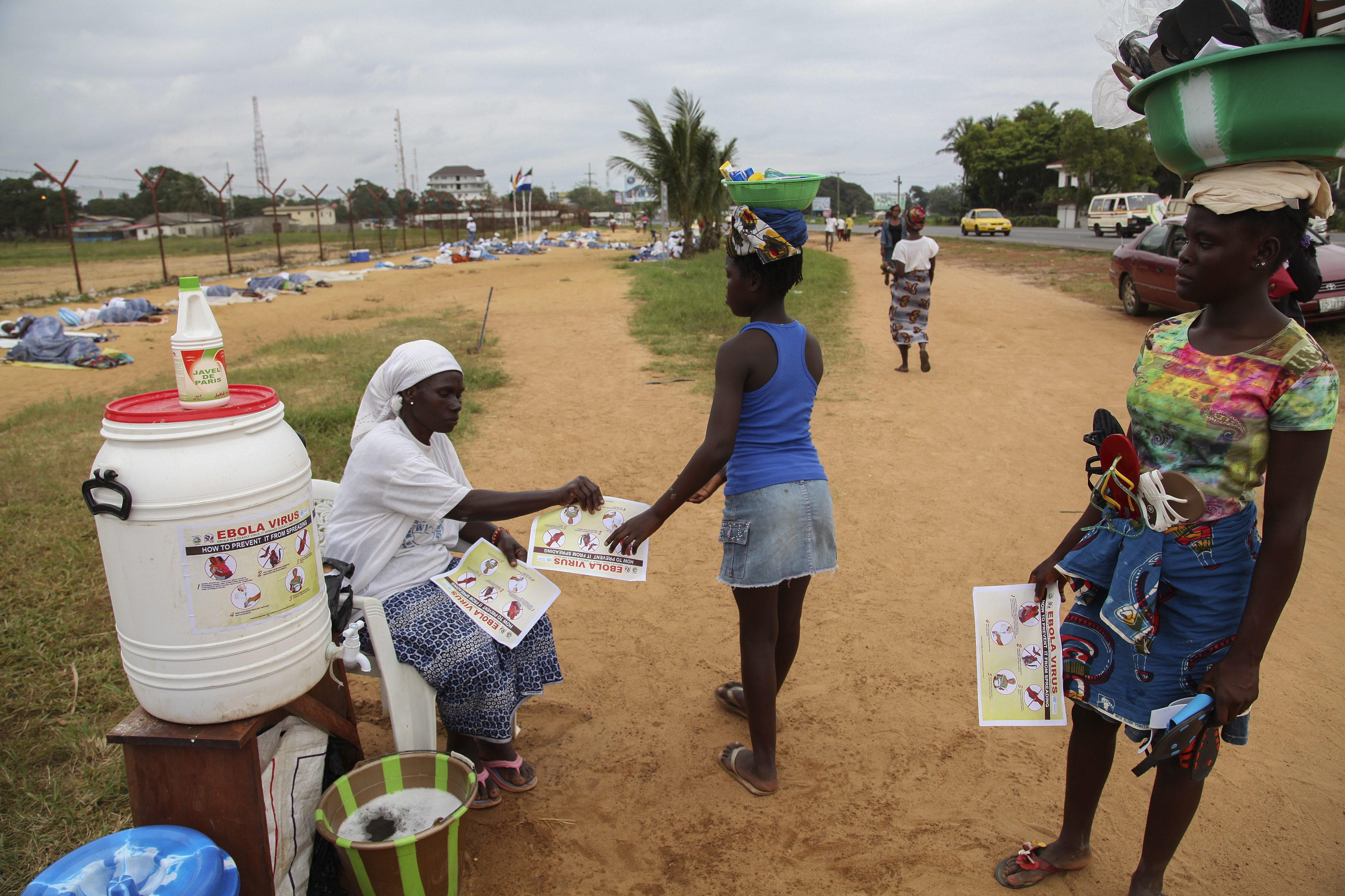 epaselect epa04350775 A Liberian woman from the Women in Peace Building Network (WIPNET) distributes Ebola sensitization information to girls at the WIPNET prayer ground in Monrovia, Liberia 12 August 2014. According to